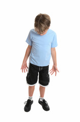Boy standing in plain blue t-shirt and shorts looking down.