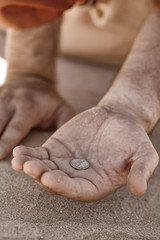 Hand holding a single coin - beggar, poverty, charity,