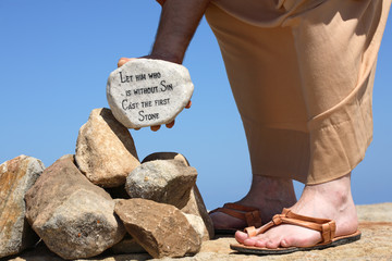 A man holds a white rock inscribed with a bible verse
