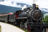 steam engine train leaving the station full of tourists-