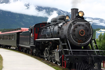 steam engine train leaving the station full of tourists