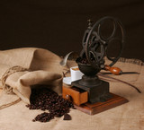 Grinder with coffee grains and a cup of expresso behind poster