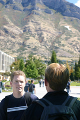 Two young male students standing and talking