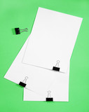 Isolated white paper with clamp on green background poster