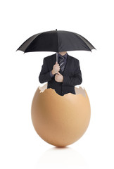 Man with an umbrella hatching out of an eggshell