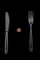 One penny lying between fork and knife