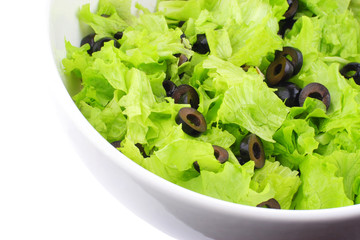 part of white dish with lettuce and slices of olives
