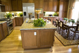 Modern kitchen with hardwood floor and island. poster