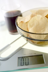 Cola and chips on the electronic balance showing 0.0kg