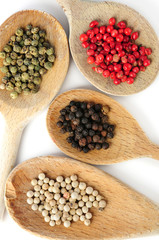 Four kinds of peppercorns in wooden cooking spoons