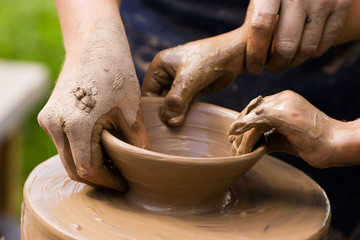 Potters hands guiding a child to help him with the ceramic wheel