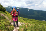 backpacker girl in red dress hiking in Carpathian mountains