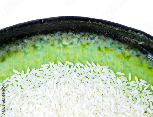 Long grain jasmine rice on green plate isolated over white.