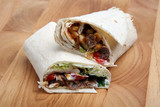 Spicy beef tortilla wrap on a wooden chopping board poster