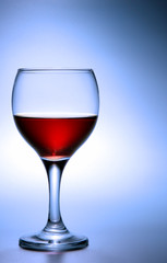 Footed glass of red wine over blue background