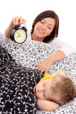 mother trying to wake up 4 years old boy /focus on alarm/ poster