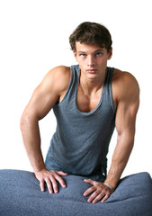 Sexy muscular man leaning on the sofa isolated on white