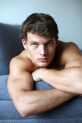 Sexy young man lying on the sofa