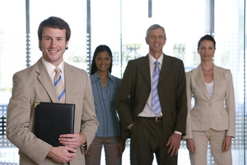 Confident young businessman with team behind him