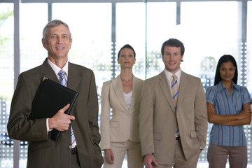 Confident mature businessman with team behind him