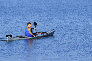 Athletic kayaker rows off into calm blue waters