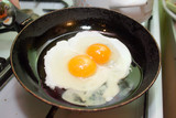 Two fried eggs in hot pan on gas stove poster