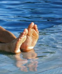 Men's feet, happy in the pool.