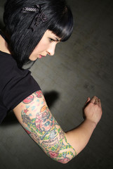 a woman with black hair and tattooed upper arm