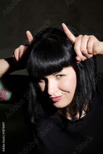 a woman with black hair and piercing shows horns
