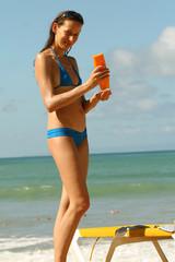 Frau cremt sich mit Sonnenschutzcreme ein