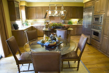 Spacious kitchen with a table and hardwood floor.
