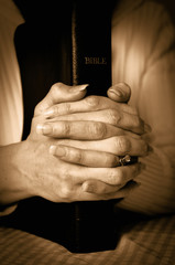 Bible and woman's hands clasped together in prayer
