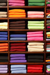 Piles of multicolored knitted woolen clothing