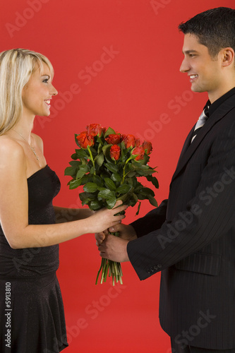 Handsome man in suit is giving beautiful woman roses