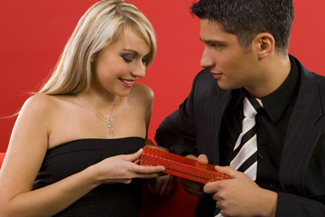 Handsome man is giving beautiful woman a gift.