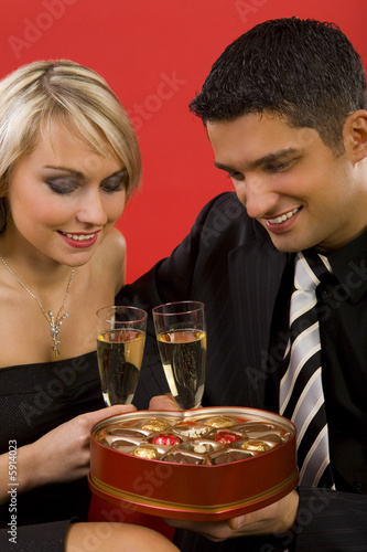 Young, sitting couple rising toast