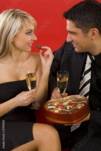 Young, sitting couple with glass of champagne in hands