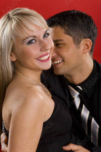 Young, hugging couple. They are looking very happy.