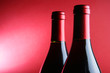 Two corked wine bottles over red background