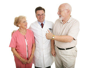 Senior couple giving a thumbs-up to their eye doctor