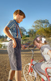 a young gentleman helps a little girl of the old tricycle poster