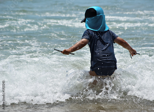 a young boy ventures into the waves at the beach