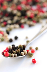 Mixed assorted peppercorns on white background macro