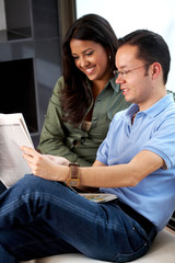casual young couple at home reading the newspaper