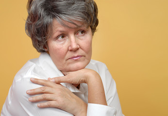 Lonely older woman in thought on yellow background