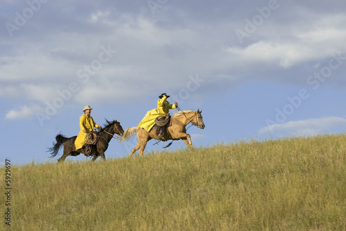 Cowboys galloping across Montana ridgeline after rainstorm