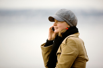 A young woman talking on a cell phone in winter.