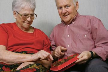 Senior couple eating chocolates