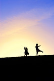 Two little girls dancing on the hill