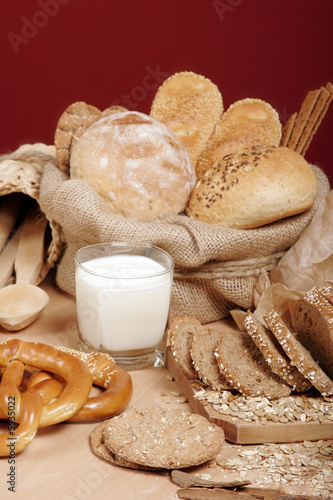 Assortment of baked breads and pretzels with a cup of yoghurt
